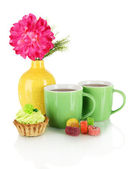 Cups of tea with candy,cake and flower isolated on white — Stock Photo
