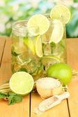 Glas cocktail med lime och mynta på träbord på ljus bakgrund — Stockfoto