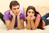 Young couple lying on carpet at home — Stock Photo