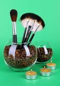 Cam kase kahve çekirdekleri, fırçalar ve yeşil zemin üzerine mum — Stok fotoğraf
