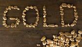 Wort gold mit goldenen steinen auf hölzernen hintergrund machen — Stockfoto