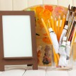 Photo frame as easel with artist's tools on wooden background - Stock Photo
