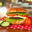 Big and tasty hamburger on table in cafe — Stock Photo