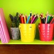 Colorful pencils in pails on shelf with copybooks on wooden background — Photo