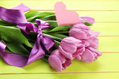 Beautiful bouquet of purple tulips on green wooden background — Stock Photo