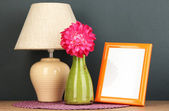 Colorful photo frame, lamp and flowers on wooden table on grey background — Stock Photo
