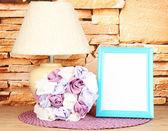 多彩相框、 灯和石头砌的墙背景上的木桌上的鲜花 — 图库照片