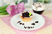 Sweet cake with blackberry and chocolate sauce on plate, with coffee, on bright background — Stock Photo