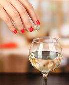 Pour something into glass with drink on wooden table on room background — Stock Photo