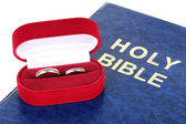 Wedding rings on bible isolated on white — Stock Photo