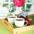 Cups of tea with flower and jam on wooden tray on table in room — Stock Photo