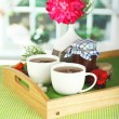 Cups of tea with flower and jam on wooden tray on table in room — Stock Photo #22006495