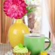 Cups of tea with cake,candy and flower on table in room — Stock Photo