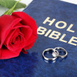 Wedding rings with rose on bible — Stock Photo