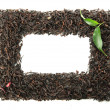 Frame of dry black tea with green leaves, isolated on white - Stock Photo