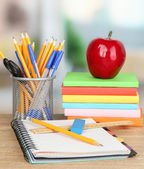 School supplies with apple on wooden table — Stok fotoğraf