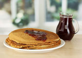 Sweet pancakes on plate with jam on table in kitchen — Stock Photo