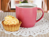 Cup of tea with cake on table in room — Stok fotoğraf