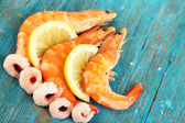 Shrimps with lemon on blue wooden table — Stock Photo