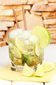 Glass of cocktail with lime and mint on white wooden table on stone wall background — Stock Photo