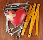 Heart and tools. Concept: Renovation of heart. On wooden background — Stockfoto