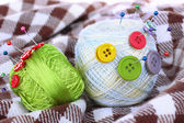 Buttons of different colors, and the two tangle thread on checked plaid — Stock Photo
