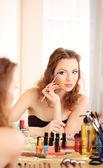 Young beautiful woman making make-up near mirror — Stock Photo