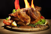 Whole roasted chicken with vegetables on plate, on flame background — Foto Stock