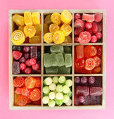 Multicolor candies in wooden box, on color background — Foto Stock