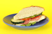 Sandwich on plate on yellow background — Stock Photo