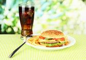 Gustoso cheeseburger con patate fritte e bevanda fredda, su sfondo luminoso — Foto Stock