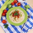 Tasty spaghetti with sauce and vegetables on plate on wooden table close-up - Photo