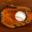 Baseball glove and ball on wooden background — Stock Photo