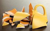 Ahşap zemin üzerine sarı kırık kupası — Stok fotoğraf