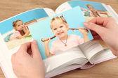 Foto nelle mani e album di foto sul tavolo di legno — Foto Stock