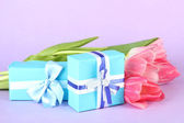 Pink tulips and gift boxes, on color background — Foto Stock