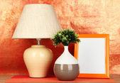 多彩相框、 灯和红色背景上的木桌上的鲜花 — 图库照片