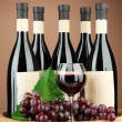 Composition of wine bottles, glasses and  grape,on wooden barrel, on brown background — Stock Photo