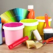Paint pots, paintbrushes and coloured swatches on wooden table on grey background — Stockfoto
