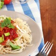 Tasty spaghetti with sauce and vegetables on plate on wooden table close-up - Stok fotoğraf