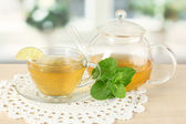 Cup of tea with mint and lime on table in room — Stock Photo