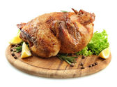 Whole roasted chicken on wooden plate with lemon, isolated on white — Stock Photo