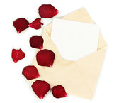 Old envelope with blank paper and dried rose petals isolated on white — Stock Photo