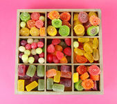 Multicolor candies in wooden box, on color background — Stock Photo