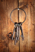 Bunch of old keys hanging on wooden wall — Foto Stock
