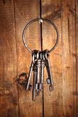 Parta starých klíčů, zavěšené na dřevěné stěně obrazce — Stock fotografie