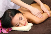Beautiful young woman in spa salon getting massage with spa stones, on dark background — Fotografia Stock