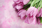Beautiful bouquet of purple tulips on pink wooden background — Stock Photo