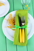 Knife and fork wrapped in napkin, on plate, on color wooden background — Stock Photo