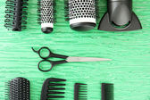 Comb brushes, hairdryer and cutting shears,on color background — Stock Photo